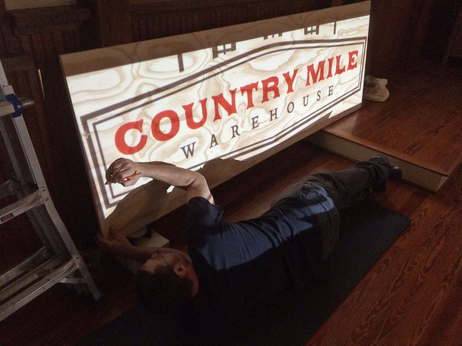 The Country Mile Warehouse logo design being applied to signage.
