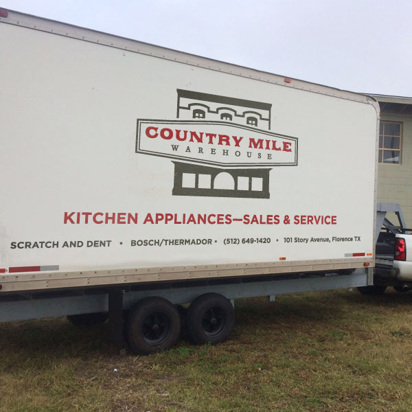 Country Mile Warehouse's logo design as applied on a trailer.